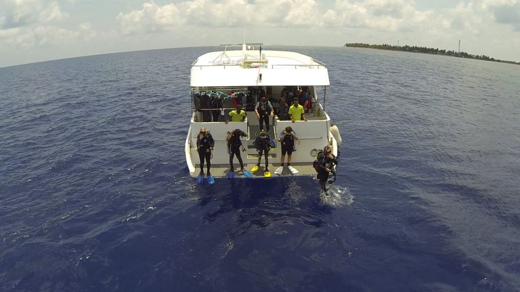Divers taking a giant stride off the dhoni in the Maldives